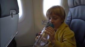 Tiro a cámara lenta de un niño pequeño que bebe el agua de la botella plástica reutilizable que se sienta en una silla a bordo de almacen de metraje de vídeo