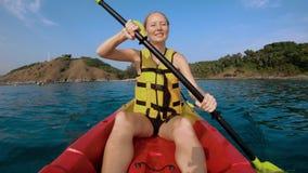Tiro a cámara lenta de una familia joven kayaking en un mar tropical y que se divierte que mira el arrecife de coral y pescados t metrajes