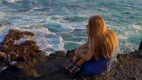 Tiro a cámara lenta de una madre y de un hijo sentándose en una roca mirando las olas oceánicas próximas el templo de la porción  almacen de video