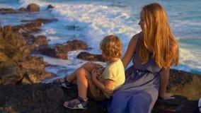 Tiro a cámara lenta de una madre y de un hijo sentándose en una roca mirando las olas oceánicas próximas el templo de la porción  almacen de metraje de vídeo
