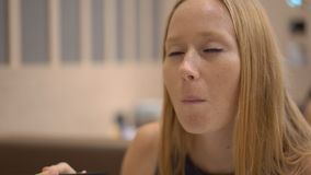Tiro a cámara lenta de una mujer joven enjoing la comida japonesa en un restaurante metrajes