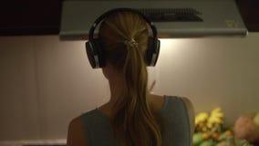 Tiro a cámara lenta de una mujer joven que cocina en el baile de la cocina en los auriculares inalámbricos metrajes