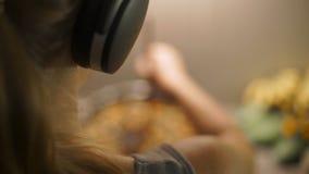 Tiro a cámara lenta de una mujer joven que cocina en el baile de la cocina en los auriculares inalámbricos almacen de metraje de vídeo