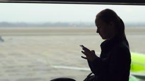 Tiro a cámara lenta de una mujer joven que usa un smartphone delante de una ventana grande en un aeropuerto almacen de metraje de vídeo