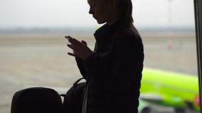 Tiro a cámara lenta de una mujer joven que usa un smartphone delante de una ventana grande en un aeropuerto almacen de video