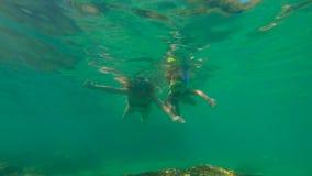 Tiro a cámara lenta de una mujer joven y de su pequeño hijo que bucean en un mar almacen de metraje de vídeo