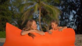 Tiro a cámara lenta de una mujer joven y de su pequeño hijo que se divierten en un sofá inflable en una playa almacen de metraje de vídeo
