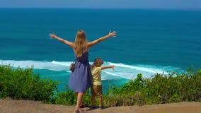 Tiro a cámara lenta de una mujer joven y de su situación del hijo en el borde del acantilado que mira el océano Suluban y Nyang almacen de metraje de vídeo