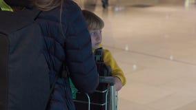 Tiro a cámara lenta de una mujer que conduce a su hijo en un carro del equipaje en el aeropuerto almacen de metraje de vídeo