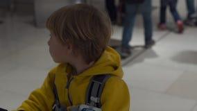 Tiro a cámara lenta de una mujer que conduce a su hijo en un carro del equipaje en el aeropuerto metrajes