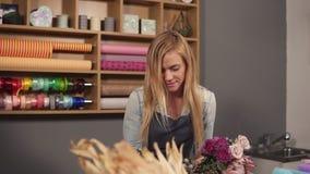 Tiro a cámara lenta del artista floral de sexo femenino rubio profesional que arregla el ramo hermoso de la boda en la floristerí almacen de metraje de vídeo