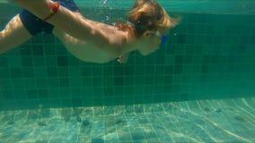 Tiro a cámara lenta del salto del niño pequeño en una piscina metrajes