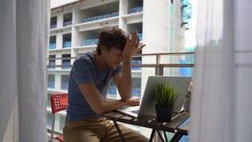 Tiro a c?mara lenta de un hombre joven que se sienta en un balc?n con un cuaderno y que sufre de un fuerte ruido producido por a metrajes