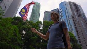 Tiro a c?mara lenta de un hombre joven que sostiene un smartphone y una bandera malasia de las ondas con los rascacielos en un fo metrajes