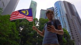 Tiro a c?mara lenta de un hombre joven que sostiene un smartphone y una bandera malasia de las ondas con los rascacielos en un fo almacen de video