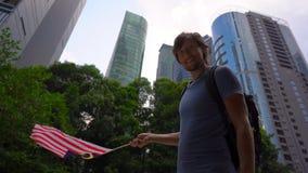 Tiro a c?mara lenta de un hombre joven que sostiene un smartphone y una bandera malasia de las ondas con los rascacielos en un fo almacen de metraje de vídeo