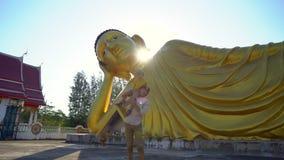 Tiro a c?mara lenta de un hombre joven y de su peque?o hijo que se divierten delante de una estatua del Buda de mentira en la isl metrajes