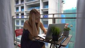 Tiro a c?mara lenta de una mujer joven que se sienta en un balc?n con un cuaderno y que sufre de un fuerte ruido producido por a metrajes