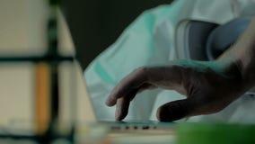 Tiro cercano de la mano del varón adulto que trabaja en el ordenador portátil El administrador de sistema soluciona el problema d almacen de video