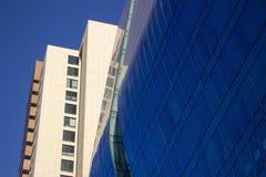 Tiro cercano de una pared azul curvada de la ventana de cristal de un edificio corporativo moderno y elegante, al lado clásico am Foto de archivo libre de regalías