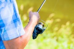 Tiro cercano del pescador del deporte que aspa en línea en la caña de pescar imagen de archivo