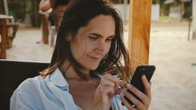 Tiro cinemático hermoso de la mujer joven feliz usando el app del comercio electrónico del smartphone que sonríe, reclinación de  metrajes
