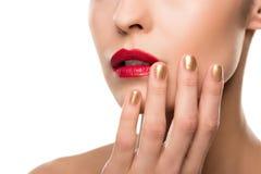 Tiro colhido da jovem mulher sensual que levanta com os bordos vermelhos lustrosos e tratamento de mãos dourado Fotografia de Stock Royalty Free