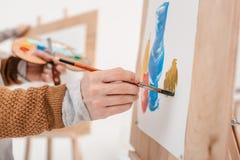 tiro colhido da pessoa que guarda o pincel e a pintura Foto de Stock