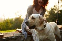 Tiro colhido da senhora africana nova que anda com o cão no parque imagens de stock