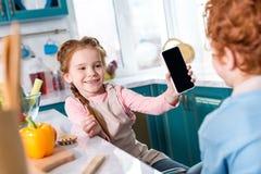 tiro colhido das crianças que usam o smartphone com tela vazia ao cozinhar junto imagem de stock royalty free