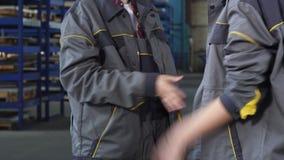 Tiro colhido de dois trabalhadores fêmeas que agitam as mãos no armazenamento da fábrica video estoque