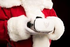 Tiro colhido de Santa Claus que guarda auriculares da realidade virtual fotos de stock royalty free