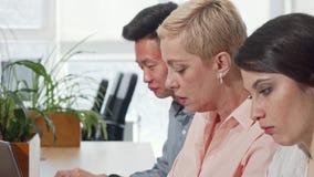 Tiro colhido de um businessteam que trabalha junto, discutindo ideias vídeos de arquivo