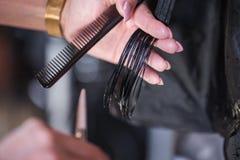 Tiro colhido de um cabelo dos clientes do corte do cabeleireiro da fêmea com as tesouras no salão de beleza imagem de stock