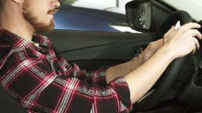 Tiro colhido de um homem farpado que senta-se em um carro que guarda o volante fotografia de stock royalty free
