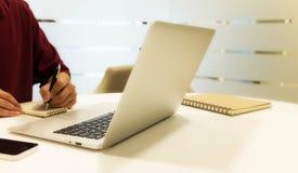 Tiro colhido de um homem novo que trabalha do portátil de utilização home Imagens de Stock Royalty Free