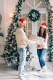 Tiro colhido de um homem surpreendente sua amiga com um presente do Natal imagens de stock