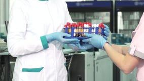 Tiro colhido de um trabalhador médico que recebe amostras da análise de sangue de um colega vídeos de arquivo