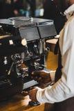 tiro colhido do barista afro-americano no avental que prepara o café na máquina do café fotos de stock