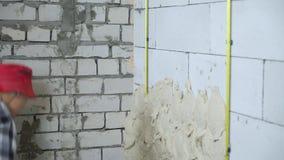 Tiro colhido do construtor que emplastra a parede ventilada do bloco de cimento filme