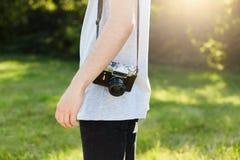 Tiro colhido do corpo masculino do ` s com a câmera retro no ombro que está na grama verde que vai a fotografar alguém Tal profis foto de stock royalty free
