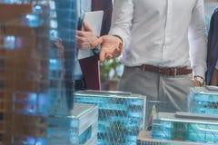 tiro colhido do homem de negócios que mostra o modelo diminuto da cidade moderna foto de stock royalty free