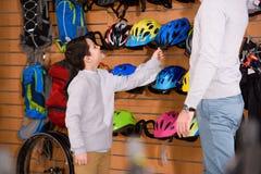 tiro colhido do pai e do filho de sorriso que escolhem capacetes da bicicleta na bicicleta fotos de stock royalty free