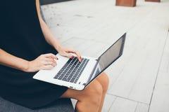 Tiro colhido do portátil de utilização fêmea novo ao sentar-se em um quintal do prédio de escritórios fotografia de stock