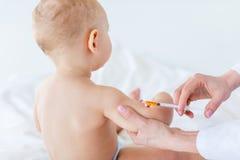 Tiro colhido do trabalhador médico que faz a injeção para o bebê bonito foto de stock royalty free