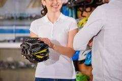 tiro colhido do vendedor de sorriso que mostra o capacete da bicicleta ao cliente imagem de stock royalty free