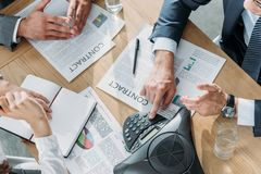 tiro colhido dos executivos que têm a conversação com contratos e speakerphone na tabela imagens de stock royalty free