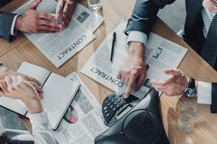 tiro colhido dos executivos que têm a conversação com contratos e speakerphone na tabela foto de stock royalty free