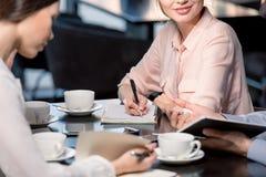 Tiro colhido dos jovens que discutem o projeto durante a reunião de negócios no café Foto de Stock