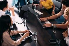 tiro colhido dos sócios comerciais multiculturais que têm a reunião na tabela com os portáteis em moderno imagens de stock royalty free